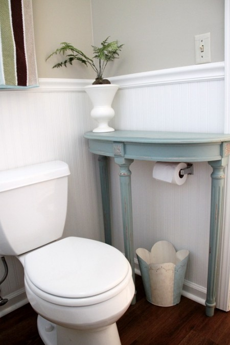 a small end table placed above a toilet paper roll is a cool bathroom storage hack