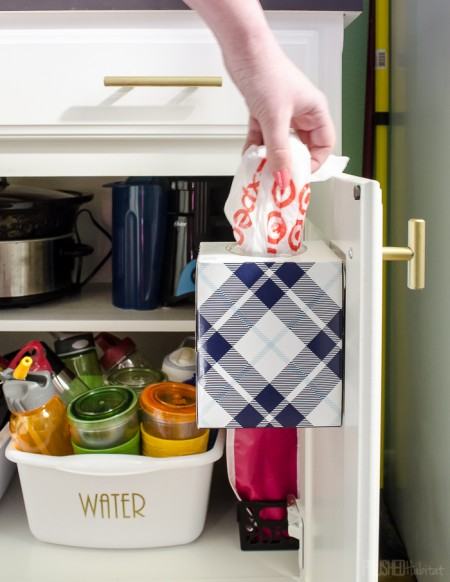 a cabinet door-mounted tissue box is perfect for storing leftover plastic shopping bags