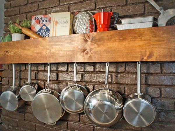 a wall-mounted wooden pot and pan rack by sam henderson is one of many genius storage hacks for small spaces
