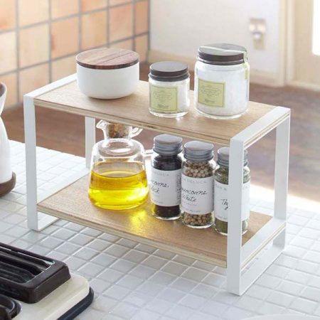 a tiny white and natural wood spice rack is a great kitchen storage solution on a budget