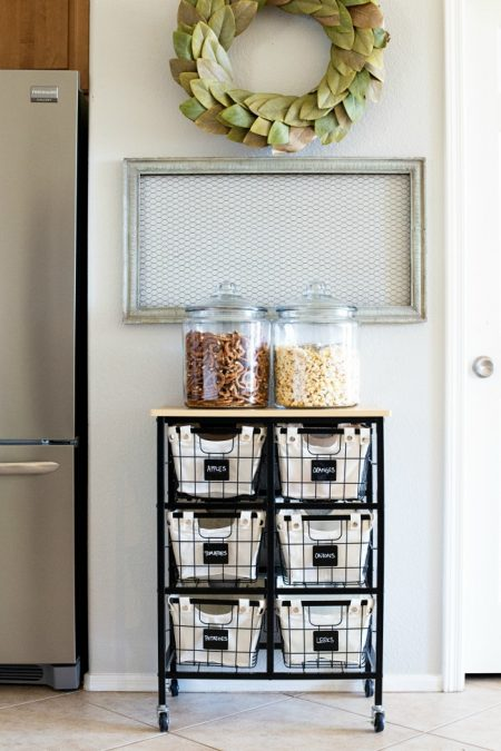 a rolling cart with canvas baskets is an easy way to store snacks and produce in a small kitchen