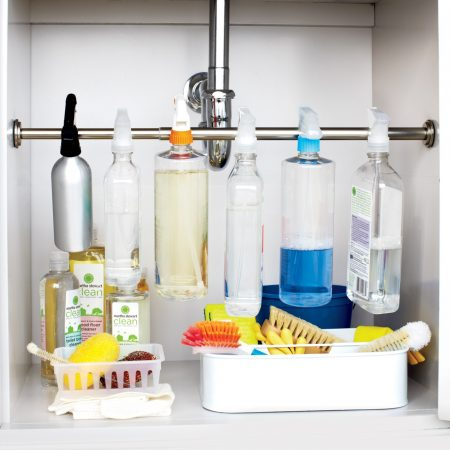 cleaning supplies storage hack: mount a tension rod underneath the kitchen sink