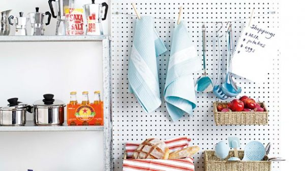 a wall-mounted diy pegboard is storing towels, cooking utensils, apples, bread, and a grocery list in a tiny kitchen