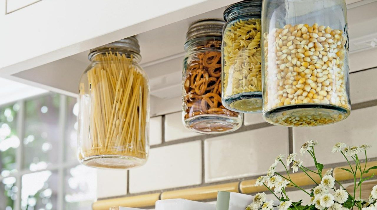 mason jars screwed into the underside of a cabinet is a creative kitchen storage hack