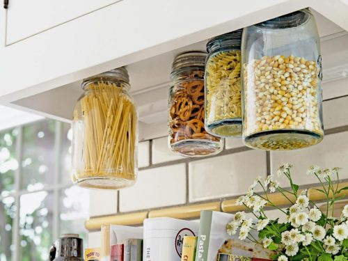 Mason jars screwed into the underside of a cabinet is a creative kitchen storage hack.