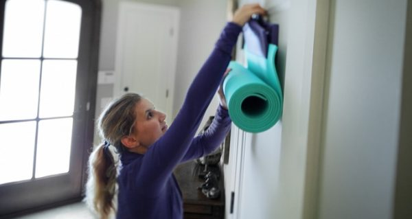 purple namaste yoga mat storage solution hung on the back of a door