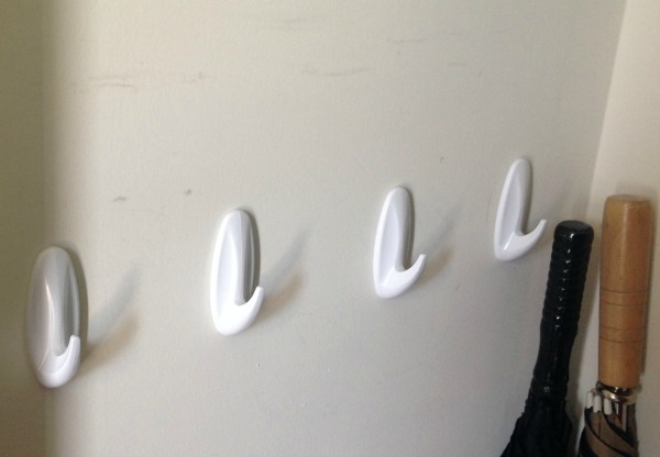 wall-mounted white coat hooks as a bedroom closet storage hack