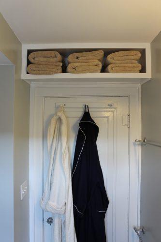 white diy storage shelf above a bathroom door