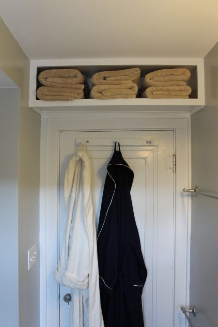 white diy storage shelf above a bathroom door