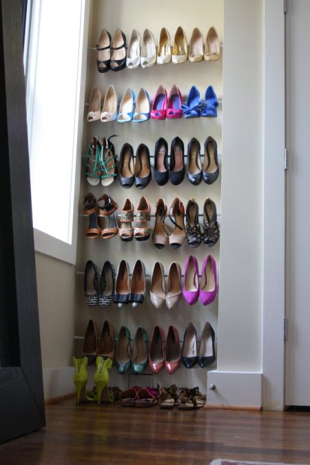 tension rod shoe racks installed in a small bedroom nook