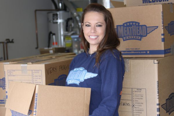 a woman wearing a blue meathead movers long sleeve shirt is smiling and carrying a moving box