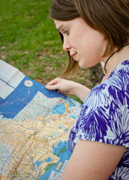 a woman wearing a white shirt with purple flowers is outside holding a map