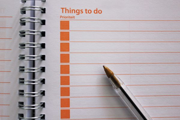 a pen on the inside of a things to do notebook is waiting for you to write your moving checklist