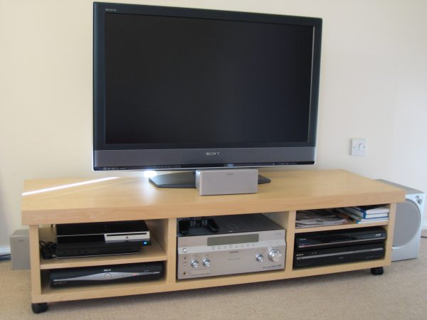 a sony flat screen tv stand with wheels is storing a sound system, speaker, playstation console, playstation controller, cable box, books, and papers