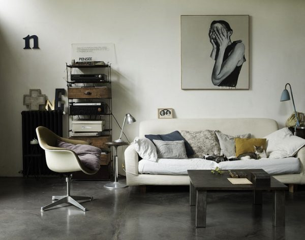 clean and organized living room with a sofa, coffee table, endtables, lamps, framed art, and a midcentury modern chair