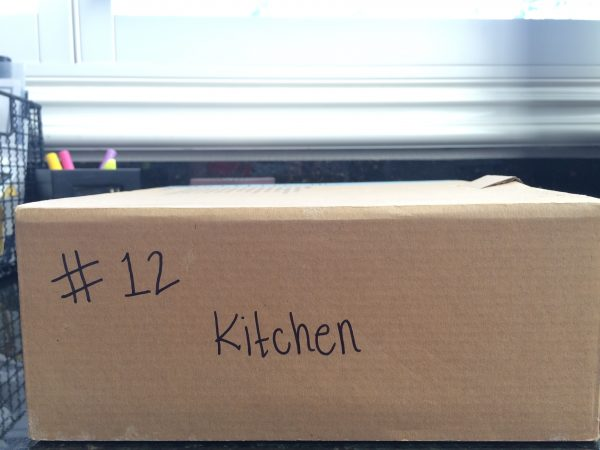 "a cardboard moving box with ""#12"" and ""kitchen"" written on the side"