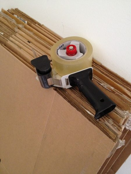 packing tape dispenser laying on folded moving and storage boxes
