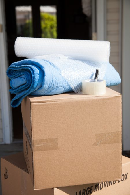 stacked moving boxes with packing tape, a moving blanket, and bubble wrap on top of the highest box