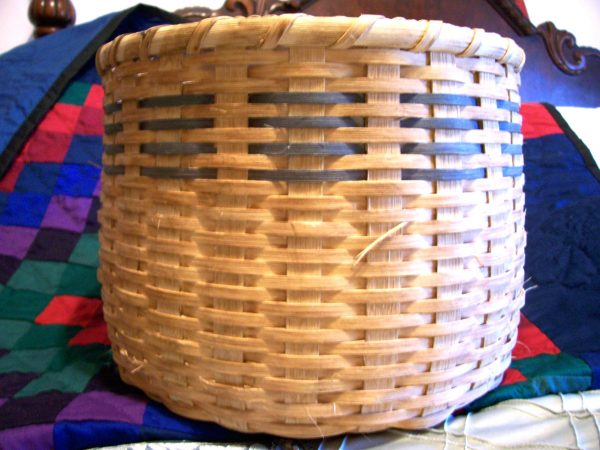 woven basket for storage on a checkered blanket in a bedroom