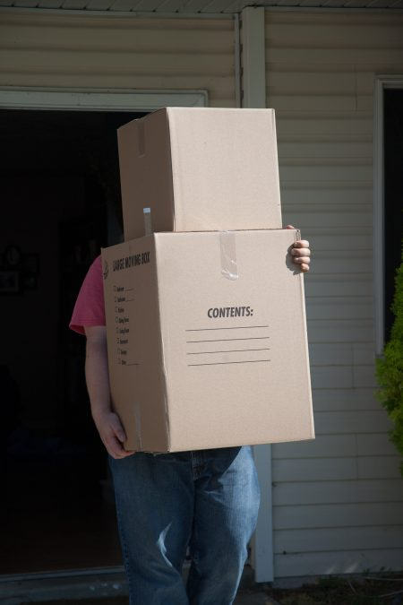 a man wearing blue jeans and a red shirt is carrying moving boxes out the door of a home