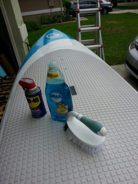 A can of WD40, surfboard, bottle of Dawn dish soap, and a brush