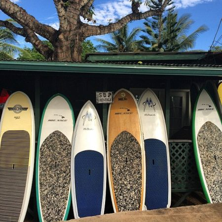 Rental SUP boards standing in the shade under a paddle board shop's roof