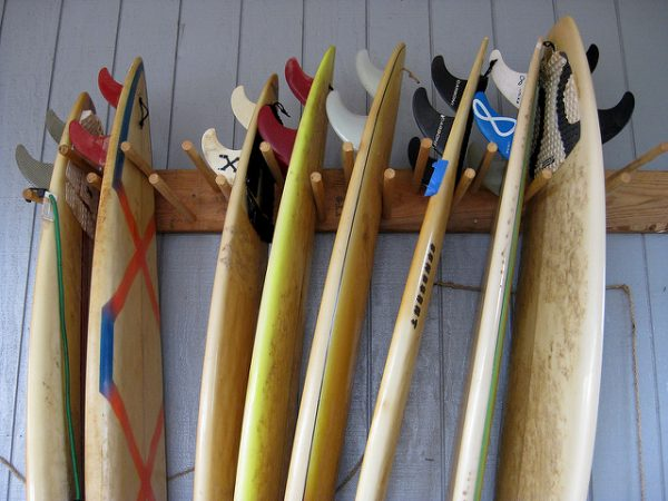 A wooden vertical surfboard rack storing 8 surfboards