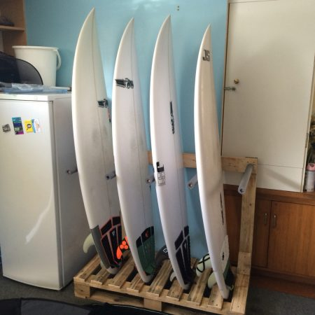 A Diy Pallet Surfboard Rack Storing 4 White Surfboards Vertically In Kitchen Next To