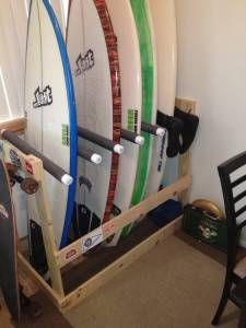 A freestanding DIY surfboard rack made from a 2x4, 1x4, PVC pipe, and pipe insulation is storing 5 surfboards vertically