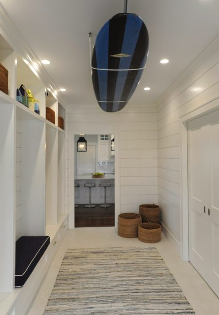 A white DIY surfboard ceiling rack is storing a black and blue-striped surfboard