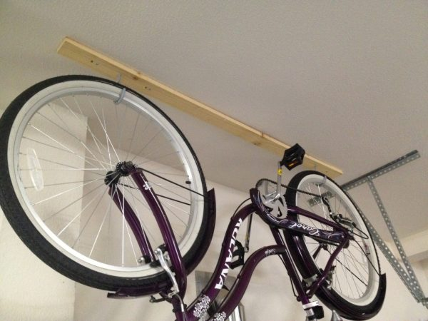 A beach cruiser hanging upside down on hooks in a garage
