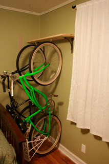A DIY beach cruiser rack made from hooks installed into a floating shelf