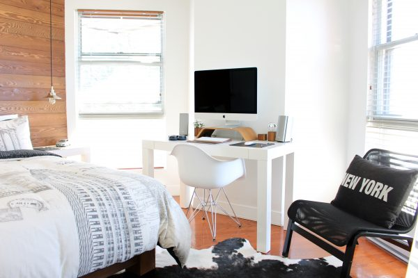 clean bedroom, desk, table, chair, new york pillow, and cowhide rug