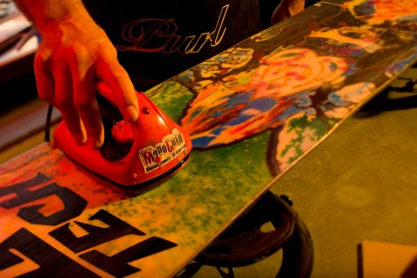 waxing a snowboard with a waxing iron