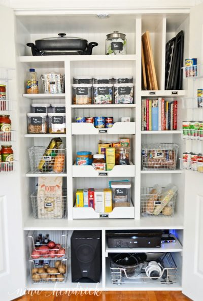 organized pantry closet with baskets, shelves, drawers, dividers, and jars