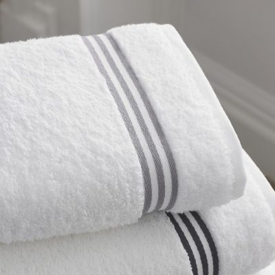stack of folded 2 clean white bathroom towels with stripes