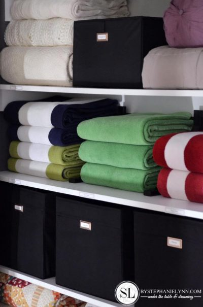 Organized Linen Closet Shelves With Storage Cubes With Lids And Folded  Towels