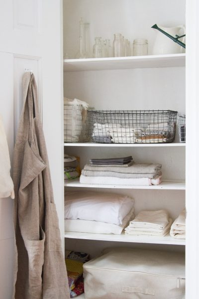 decluttered linen closet with fabric bags, storage crates, and folded bed sheets and bath towels