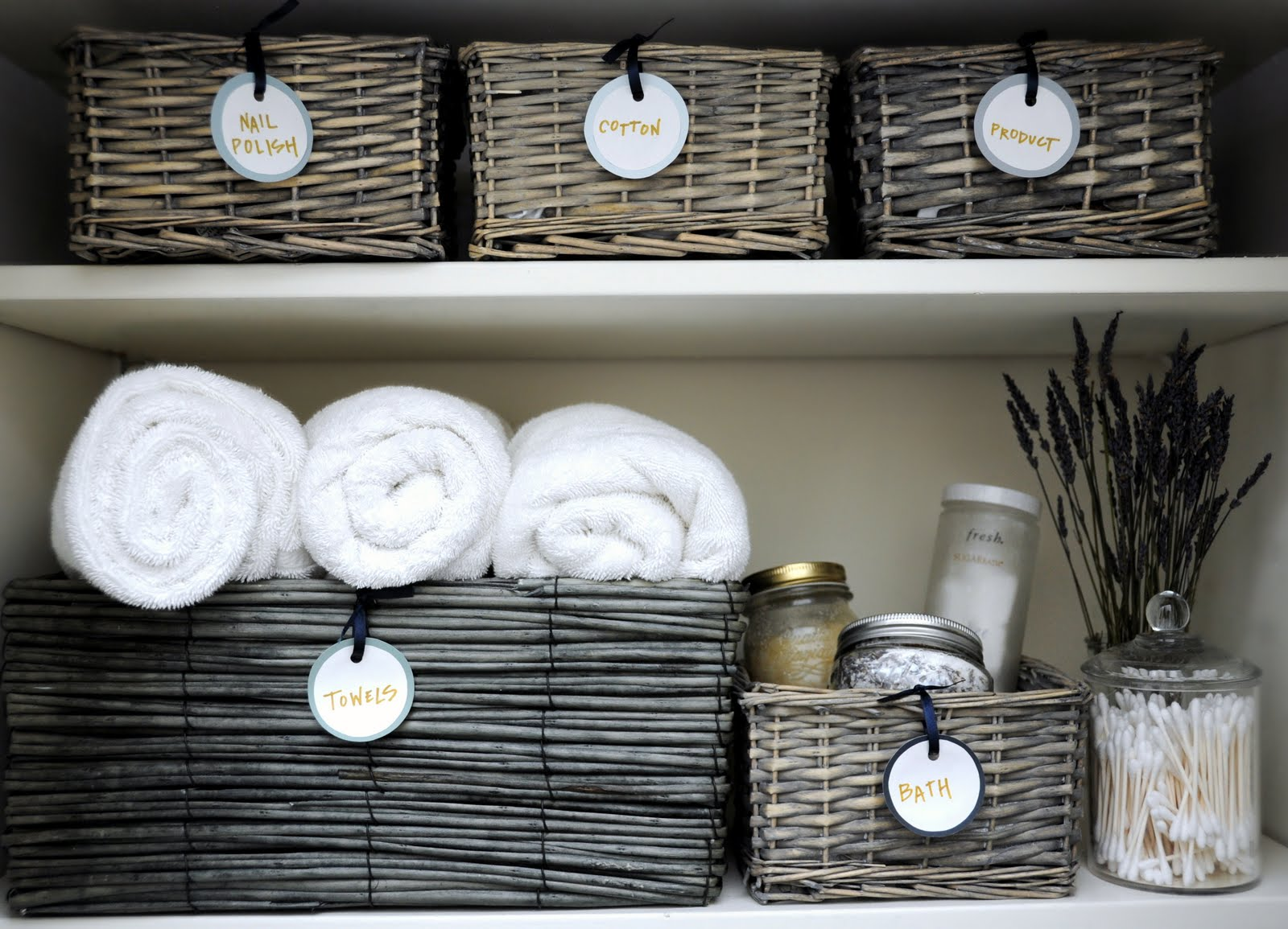 how to organize linen closet: declutter, sort by category, and store things in storage baskets with labels