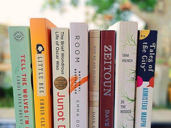 8 books on a bookshelf at a booksale