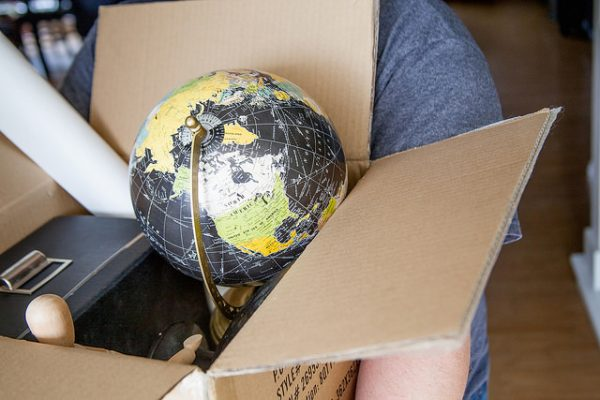 cardboard box for packing and moving globe, wooden figurine, poster, and more
