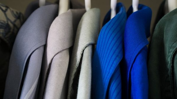 blue, green, and gray collared shirts hanging on white hangers in a closet