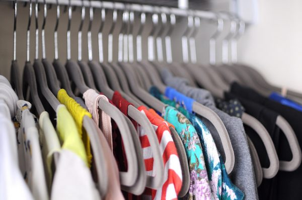 shirts hanging on gray felt hangers in an organized closet