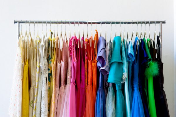 rolling clothes rack hanging color-coded shirts