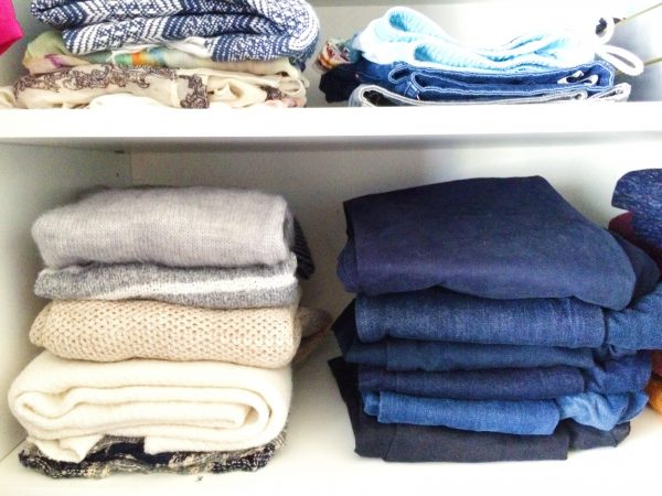 denim and sweaters stacked on closet shelves