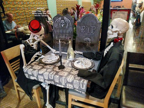 halloween skeletons sitting at a dining table