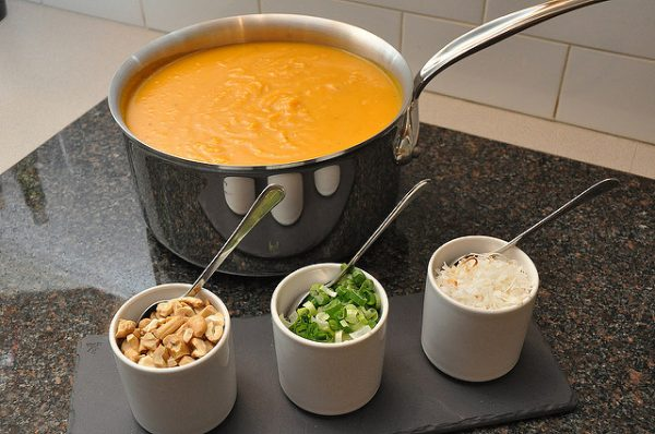 roasted butternut squash soup in a pot next to condiments on a kitchen counter