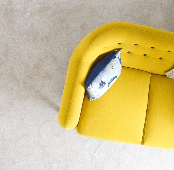 throw pillow on a yellow futon in a living room