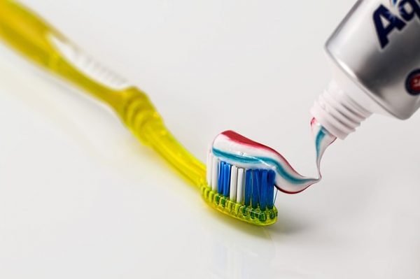 squeezing toothpaste onto a toothbrush