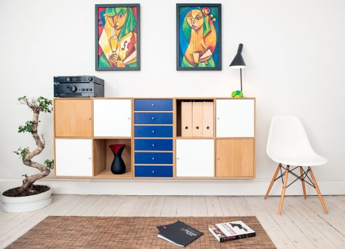 decluttered room with wall storage cubes, a plant, a white mid-century modern chair, and 2 paintings hanging on the wall